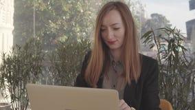 Η γυναίκα κουβεντιάζει από τα κοινωνικά δίχτυα χρησιμοποιώντας το lap-top στο χρόνο σπασιμάτων στην εργασία φιλμ μικρού μήκους