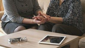 Η γυναίκα κρατά ένα ζαρωμένο χέρι μιας ηλικιωμένης γυναίκας απόθεμα βίντεο