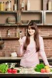 Η γυναίκα κρατά ένα κουτάλι στο χέρι της Νέο μαγείρεμα γυναικών στην κουζίνα στο σπίτι τρόφιμα υγιή σιτηρέσιο Στοκ Εικόνα