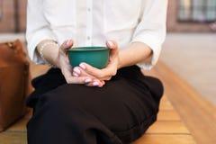 Η γυναίκα κρατά ένα σμαραγδένιο κύπελλο με το πράσινο τσάι matcha στα χέρια της πέρα από τον πράσινο μεταλλικό πίνακα στο εσωτερι Στοκ φωτογραφία με δικαίωμα ελεύθερης χρήσης