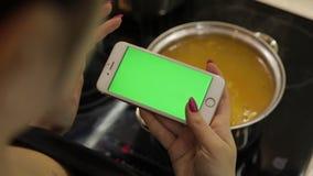 Η γυναίκα κρατά ένα smartphone με μια πράσινη οθόνη, και τη μαγειρεύοντας σούπα φιλμ μικρού μήκους