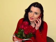 Η γυναίκα κρατά μια ανθοδέσμη των κόκκινων τριαντάφυλλων διαθέσιμων και μιλά με το κινητό τηλέφωνο στοκ φωτογραφία