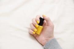 Η γυναίκα κρατά μια κίτρινη στιλβωτική ουσία καρφιών Στοκ Φωτογραφίες