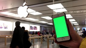 Η γυναίκα κρατά μια κενή έξυπνη συσκευή με μια πράσινη οθόνη για το περιεχόμενο συνήθειάς σας απόθεμα βίντεο