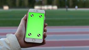 Η γυναίκα κρατά μια κενή έξυπνη συσκευή με μια πράσινη οθόνη φιλμ μικρού μήκους