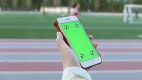 Η γυναίκα κρατά μια κενή έξυπνη συσκευή με μια πράσινη οθόνη απόθεμα βίντεο