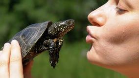 Η γυναίκα κρατά μια μικρή χελώνα ποταμών στα χέρια της κοντά στο πρόσωπο στη φύση κίνηση αργή φιλμ μικρού μήκους