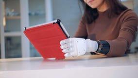 Η γυναίκα κρατά μια ταμπλέτα με το ρομποτικό χέρι, κλείνει επάνω απόθεμα βίντεο