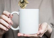 Η γυναίκα κρατά την άσπρη κούπα στα χέρια Πρότυπο σχεδίου Στοκ Εικόνες