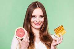 Η γυναίκα κρατά την βιταμίνη C πακέτων γκρέιπφρουτ και φουσκαλών χαπιών Στοκ φωτογραφία με δικαίωμα ελεύθερης χρήσης