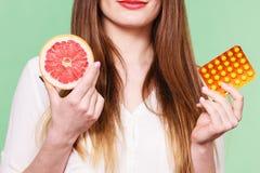 Η γυναίκα κρατά την βιταμίνη C πακέτων γκρέιπφρουτ και φουσκαλών χαπιών Στοκ εικόνα με δικαίωμα ελεύθερης χρήσης