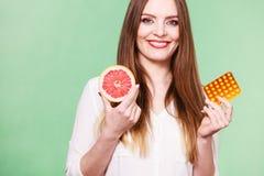 Η γυναίκα κρατά την βιταμίνη C πακέτων γκρέιπφρουτ και φουσκαλών χαπιών Στοκ Εικόνα