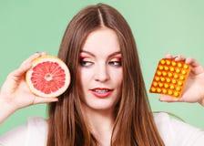 Η γυναίκα κρατά την βιταμίνη C πακέτων γκρέιπφρουτ και φουσκαλών χαπιών Στοκ Φωτογραφία