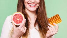 Η γυναίκα κρατά την βιταμίνη C πακέτων γκρέιπφρουτ και φουσκαλών χαπιών Στοκ φωτογραφίες με δικαίωμα ελεύθερης χρήσης