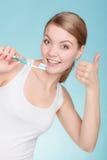 Η γυναίκα κρατά την οδοντόβουρτσα με τα καθαρίζοντας δόντια οδοντόπαστας Στοκ Εικόνες