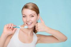 Η γυναίκα κρατά την οδοντόβουρτσα με τα καθαρίζοντας δόντια οδοντόπαστας Στοκ εικόνα με δικαίωμα ελεύθερης χρήσης