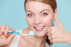 Η γυναίκα κρατά την οδοντόβουρτσα με τα καθαρίζοντας δόντια οδοντόπαστας Στοκ εικόνες με δικαίωμα ελεύθερης χρήσης