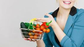 Η γυναίκα κρατά το καλάθι αγορών με τα λαχανικά στοκ φωτογραφία