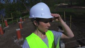 Η γυναίκα κρατά το κράνος και το γράψιμο κοντά στο εργοτάξιο οικοδομής απόθεμα βίντεο