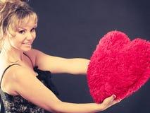Η γυναίκα κρατά το μεγάλο κόκκινο σύμβολο αγάπης καρδιών Στοκ Εικόνες