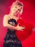 Η γυναίκα κρατά το μεγάλο κόκκινο σύμβολο αγάπης καρδιών Στοκ φωτογραφία με δικαίωμα ελεύθερης χρήσης