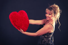 Η γυναίκα κρατά το μεγάλο κόκκινο σύμβολο αγάπης καρδιών Στοκ Εικόνα