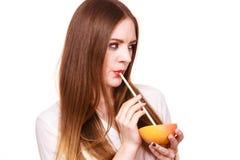 Η γυναίκα κρατά το χυμό κατανάλωσης γκρέιπφρουτ από τα φρούτα Στοκ εικόνες με δικαίωμα ελεύθερης χρήσης