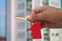 Η γυναίκα κρατά ότι ένα κλειδί σε την παραδίδει το μέτωπο μιας πολυκατοικίας στοκ εικόνες