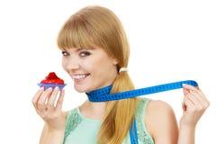Η γυναίκα κρατά cupcake και μετρώντας την ταινία σιτηρέσιο Στοκ Εικόνα