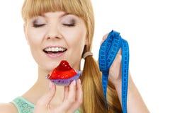 Η γυναίκα κρατά cupcake και μετρώντας την ταινία σιτηρέσιο Στοκ Εικόνες
