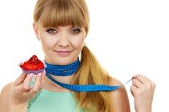 Η γυναίκα κρατά cupcake και μετρώντας την ταινία σιτηρέσιο Στοκ φωτογραφία με δικαίωμα ελεύθερης χρήσης