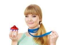 Η γυναίκα κρατά cupcake και μετρώντας την ταινία σιτηρέσιο Στοκ εικόνες με δικαίωμα ελεύθερης χρήσης