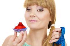 Η γυναίκα κρατά cupcake και μετρώντας την ταινία σιτηρέσιο Στοκ εικόνα με δικαίωμα ελεύθερης χρήσης