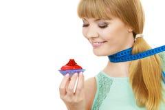 Η γυναίκα κρατά cupcake και μετρώντας την ταινία σιτηρέσιο Στοκ Φωτογραφίες