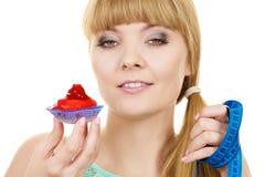 Η γυναίκα κρατά cupcake και μετρώντας την ταινία σιτηρέσιο Στοκ Φωτογραφία