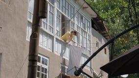 Η γυναίκα κρεμά τα ενδύματα στο σχοινί απόθεμα βίντεο