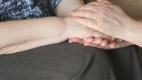 Η γυναίκα κτυπά χέρι μιας ηλικιωμένης το ζαρωμένο γυναίκας φιλμ μικρού μήκους