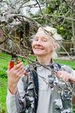 Η γυναίκα κόβει έναν κλάδο σε ένα Apple-δέντρο στον κήπο Στοκ Εικόνες