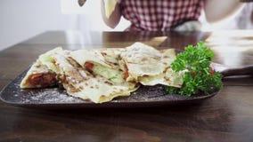 Η γυναίκα κόβει και τρώει το μεξικάνικο χορτοφάγο quesadilla απόθεμα βίντεο