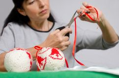 Η γυναίκα κόβει μια κόκκινη κορδέλλα με το ψαλίδι για να κάνει ένα τόξο για το christma Στοκ Εικόνες
