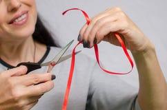 Η γυναίκα κόβει μια κόκκινη κορδέλλα με το ψαλίδι για να κάνει μια διακόσμηση Στοκ εικόνες με δικαίωμα ελεύθερης χρήσης