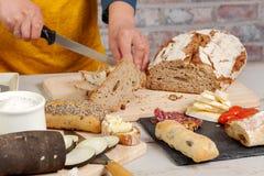 Η γυναίκα κόβει μια παραδοσιακή φέτα ψωμιού Στοκ Φωτογραφίες