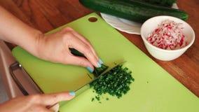 Η γυναίκα κόβει τα φρέσκα φρέσκα κρεμμύδια στην κουζίνα στον ξύλινο πίνακα απόθεμα βίντεο