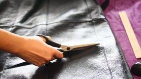 Η γυναίκα κόβει τα sheepskin παλτά Κόβει sheepskin με ένα ζευγάρι sheepskin των παλτών και διαδίδει την περικοπή φιλμ μικρού μήκους