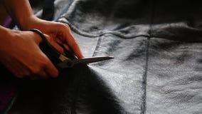Η γυναίκα κόβει τα sheepskin παλτά Κόβει sheepskin με ένα ζευγάρι sheepskin των παλτών και διαδίδει την περικοπή απόθεμα βίντεο