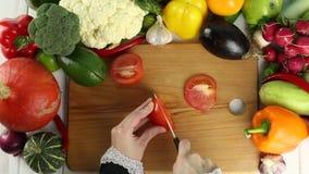 Η γυναίκα κόβει την κόκκινη ντομάτα μεταξύ των φρέσκων λαχανικών φιλμ μικρού μήκους