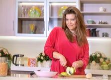 Η γυναίκα κόβει τη Apple με ένα μαχαίρι Στοκ Εικόνα
