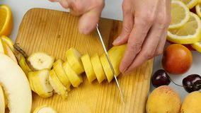 Η γυναίκα κόβει τις φέτες μπανανών δίπλα-δίπλα σε έναν τέμνοντα πίνακα βάζει τα κομμάτια περικοπών της μπανάνας κίνηση αργή απόθεμα βίντεο