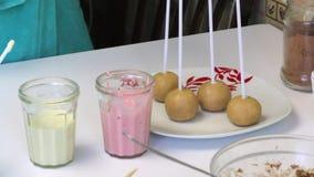 Η γυναίκα κόλλησε chopsticks της στις σφαίρες σφουγγαριών για να κάνει τα λαϊκά κέικ Κοντά στον πίνακα είναι γυαλιά με την τήξη φιλμ μικρού μήκους