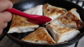 Η γυναίκα λέει το μεσημεριανό γεύμα, τρίγωνα κρέατος από το pita στα τηγανητά σε ένα τηγάνι απόθεμα βίντεο